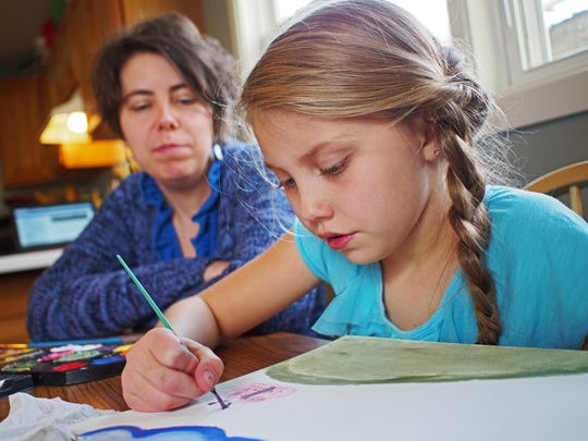 Mady Theisen, 9, a 4th-grade student who is homeschooled, works on a painting as her mom, Brooke Theisen, looks on Tuesday, Nov. 15, 2016, at their home in Sioux Falls.