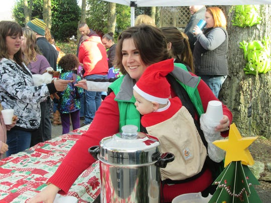 Co-Owner Nicole Bucher offers an attendee a hot chocolate at the registration tent.