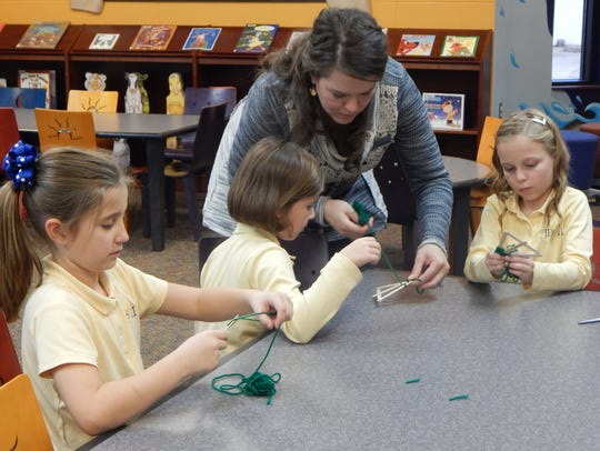 Library aide Christa Duke shows students Macy Gough,