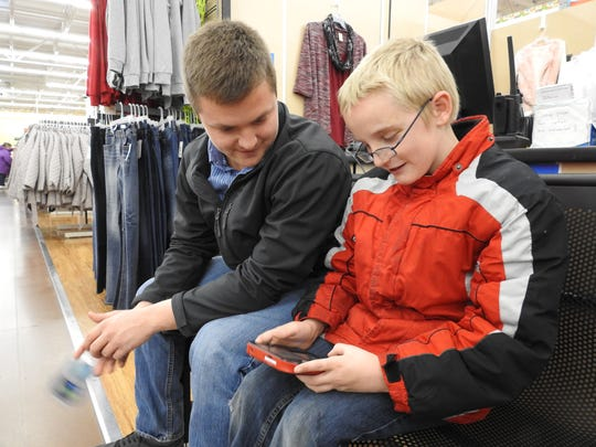 Blake Corder, right, shows shopper Phil Goerig his Pokemon game while the two wait for Corder's brother to try on his new winter clothes.