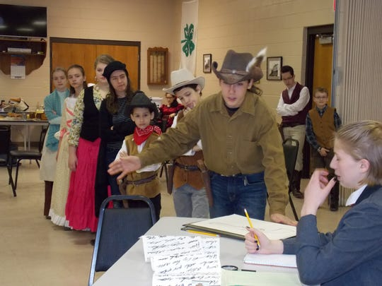 The townsfolk from Low Humidity Chasm wait in line to register for the census at the bank while Banker Richard Coldheart, played by Jenna Soldner, takes down the necessary information from Deputy DooWrong, played by John Schauer. Pictured are, from left: Kayla Doll, Sarah Doll, Ashlianna Murphy, Neve Schauer, Seth Steffes, Caleb Steffes, John Schauer and Jenna Soldner. Pictured in the background, from left, are Christian Steffes and Michael Doll.