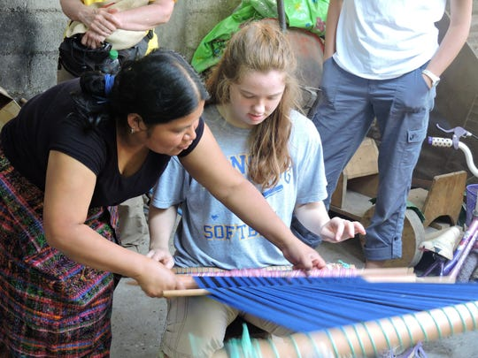 Clara Montague learns to weave on the traditional Guatemalan loom. The Lansing Youth Mission members went to San Lucas Toliman to see the results of their fundraising and to work on the projects they support.