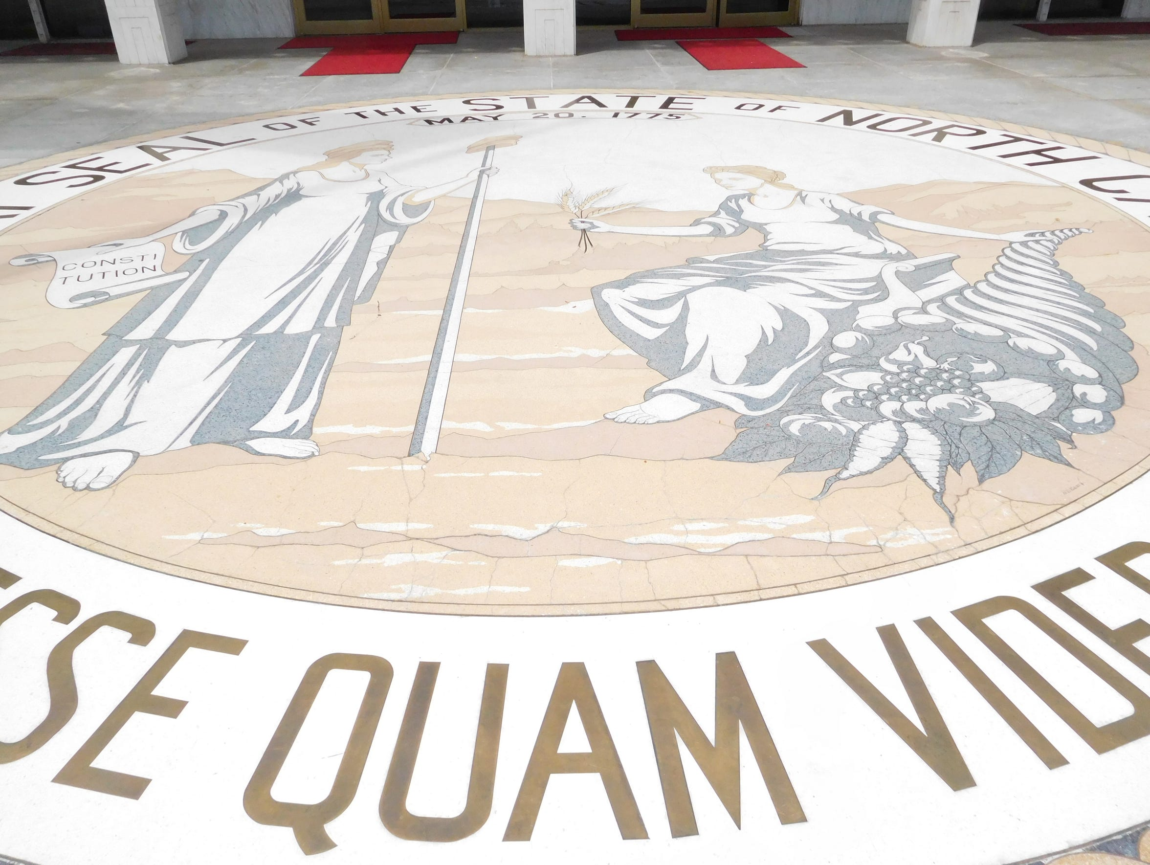 The N.C. state seal is embedded in the floor of the