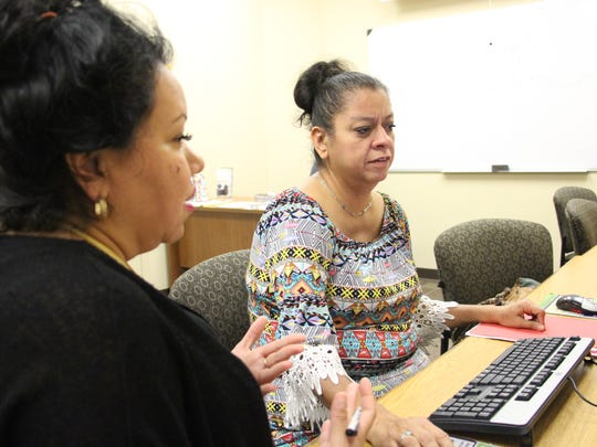 Victoria Luce Prewitt (left) helps Laura Fearon use a program on the computer Friday, June 16, 2017, at Coastal Compass Educational and Career Resource Center.