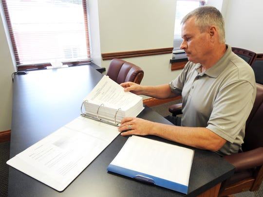 Coshocton County Court Administrator Doug Schonauer displays the book of forms used for cases.