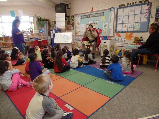 A law enforcement officer visits a Desert Sands preschool class to talk about public safety.