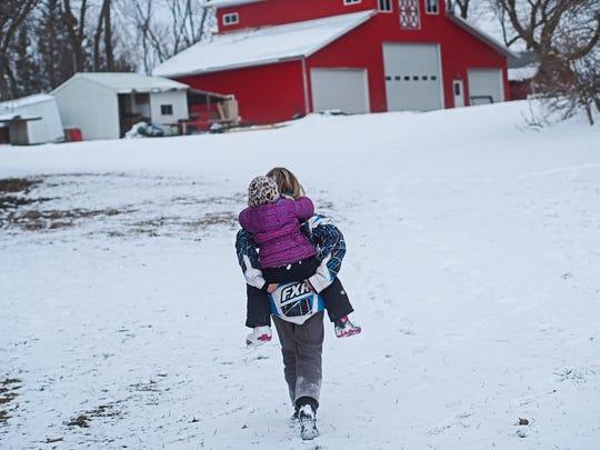 Makenzee, 12, carries her sister Faith Graham, 3, back