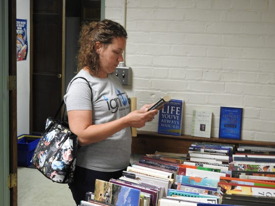 Jessica Mitchell looks over the books Thursday at the