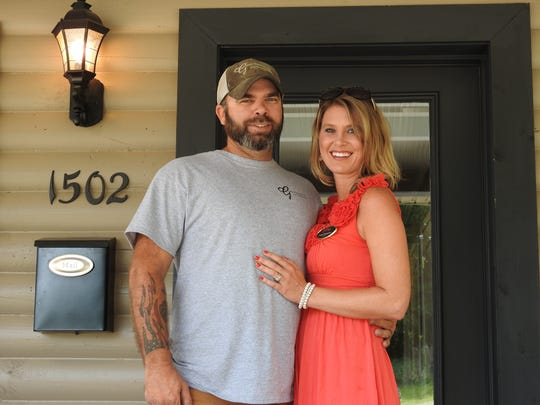 Jason and Carly Thompson stand on the porch of the new HER Realtors office. The office was constructed from a wooden cabin the couple came across through their Grason Properties and Construction business.