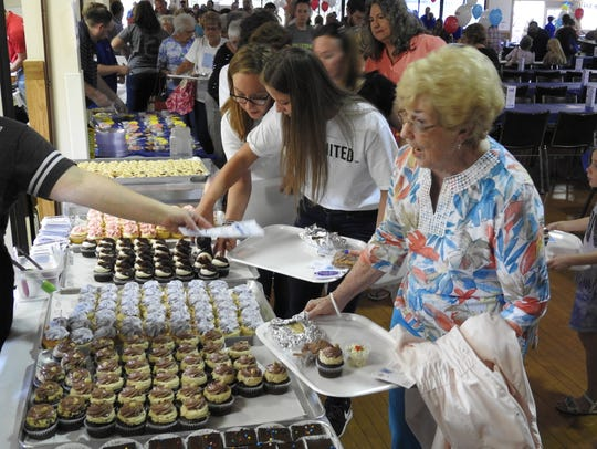 Joan McNeely of Coshocton receives a cupcake and menu