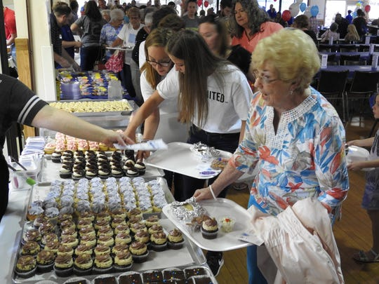 Joan McNeely of Coshocton receives a cupcake and menu from Hannah Marie's Thursday at Taste of Coshocton held at Lake Park Pavilion.