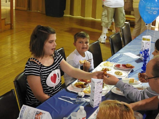 Mattalyn Keiser, 11, shares a bite with her mother, Crystal Keiser, Thursday at the Taste of Coshocton at Lake Park Pavilion. Maison Keiser, 8, liked the noodles from Schumaker Farms and the chips and cheese from the Yucatan.