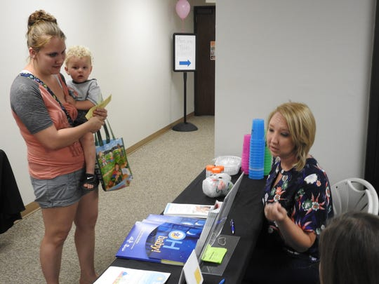 Chelsea Moore with her son, Colin Lewis, 1, speak with Rachel Murphy about services offered by Help Me Grow at a nutritional fair Thursday by Coshocton County WIC.