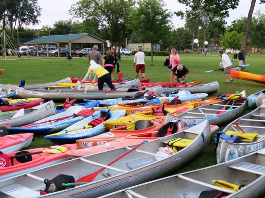Watercraft from Heavner Canoe & Kayak Rental sit in Central Park during the monthly Moonlight Paddle. Paddlers make their way to the park, spend time in downtown Milford, and then paddle back to Heavner's by moonlight.