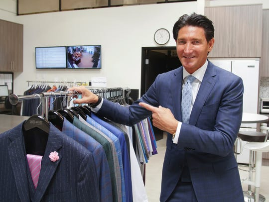 David August Heil shows off a rack of suits designed
