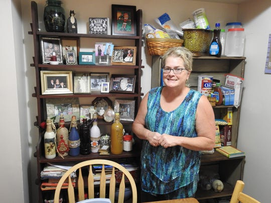 Beth Winner stands in her home at the Meadows. A bookcase filled with family photos and mementos can be seen behind Winner, who said she and her family are happy to be living in their apartment.