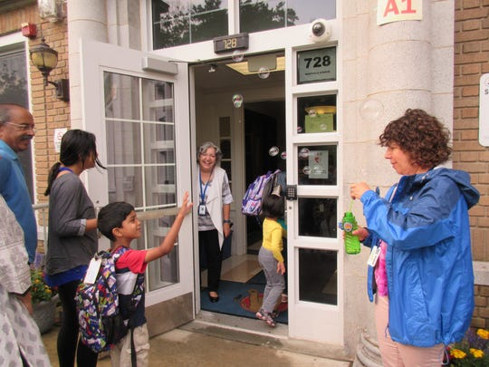 The threat of rain did not dampen the spirit of Lincoln School Pre-K teacher Andrea Taylor who greeted all of the children approaching the school on their first day on Wednesday, Sept. 6, with celebratory bubbles. Kindergartner Siddhant Nair appreciated the special reception, and was welcomed next by Principal Audrey Zavetz who met each child entering the school.
