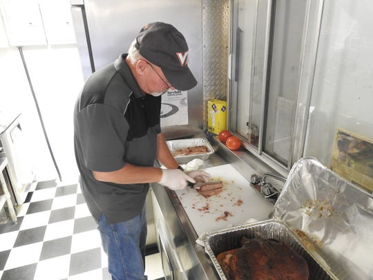 Andy Rittberger slices a brisket in preparation for