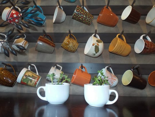 A display of coffee mugs is nestled above the fireplace.