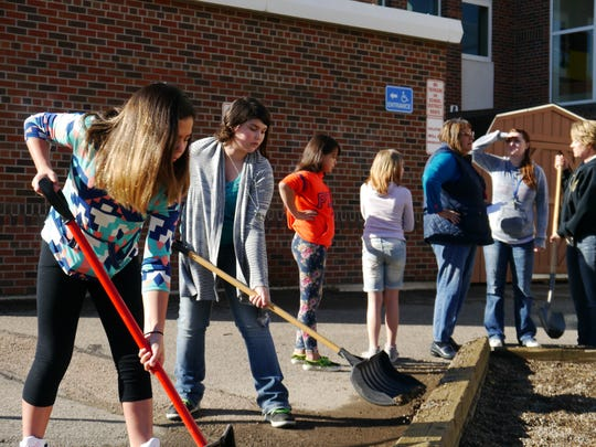 Student volunteers shovel gravel back into the play area at Whittier Elementary School Saturday.