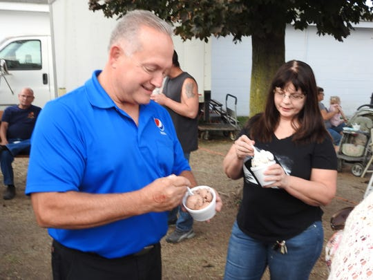 Ed and Diane Kent eat ice cream from the Little Ice Cream Barn at the Coshocton County Fair.