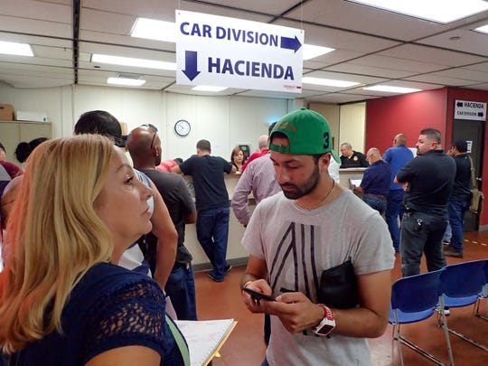 Puerto Ricans wait in line at a  Hacienda tax office at the Crowley Maritime Corp. shipping terminal at the Port of San Juan on Oct. 6, 2017.