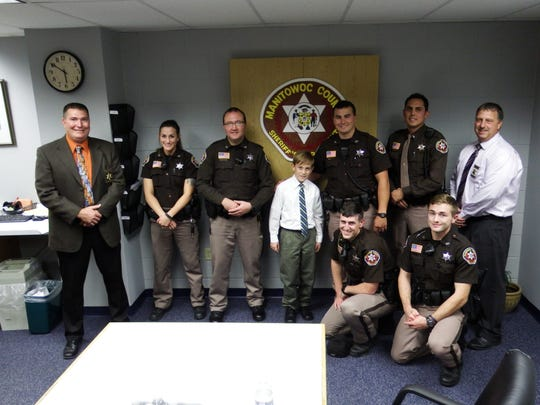 Nathan Hawke with members of the Manitowoc County Sheriff's Office. Hawke, 10, of Two Rivers, was honored by the department on Oct. 10 for his efforts in helping to save his 6-year-old cousin's life in August.