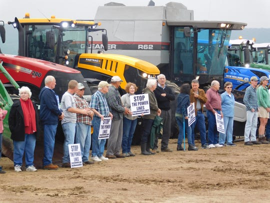 About 40 people lined up in front of farm equipment
