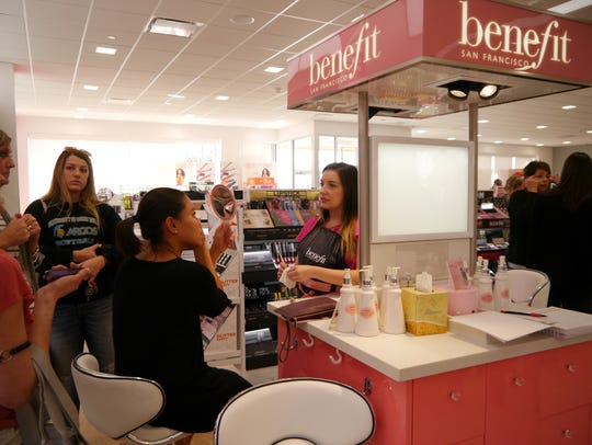 Sarah Maki, right, helps customers at the Benefit counter