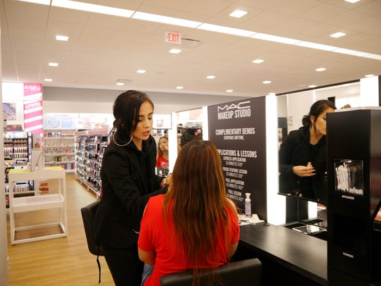 Marisa Rodriguez helps a customer at the MAC Cosmetics