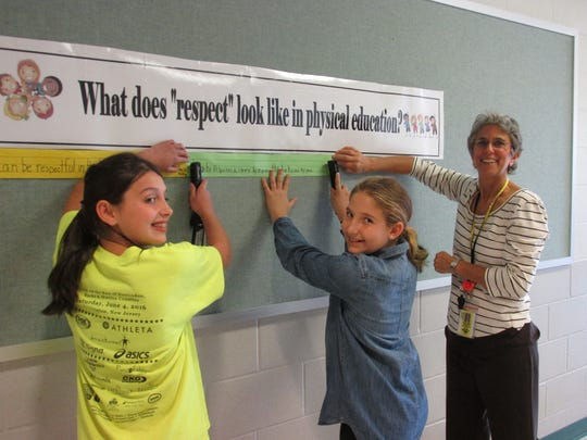 Hannah Kavanaugh, Emily Steinberg and Barbara Pauley begin to decorate a hallway bulletin board.