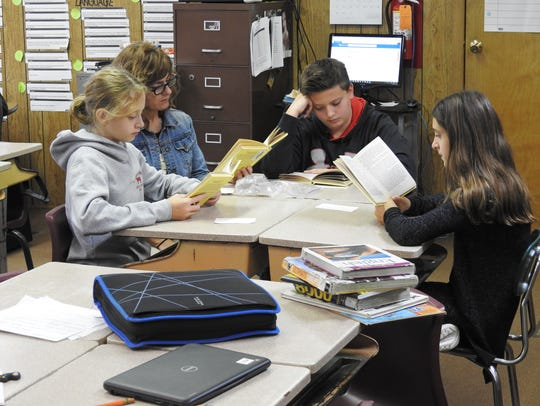 Teacher Gwenna Neal works with sixth-grade students