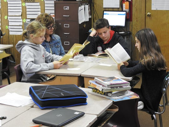 """Teacher Gwenna Neal works with sixth-grade students Joshua Woolard, Courtney Bookless and Jayden Rice on reading """"The Witch of Blackbird Pond"""" at Keene Elementary School. Consolidating elementary buildings is one thing the district may look at to compensate for a loss of $1.18 million in tax revenue from the devaluation of the AEP plant in Conesville."""