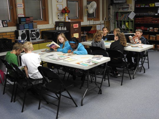 Fourth-grade students of Stephanie Kopec read in the library of Keene Elementary School. Consolidating elementary buildings is one thing the district may consider to compensate for a loss of $1.18 million in tax revenue from the devaluation of the AEP plant in Conesville.