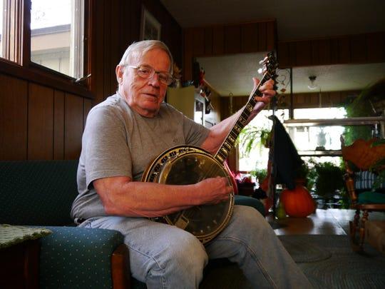 Bob McKinnon shows off his banjo skills in his Great Falls home.