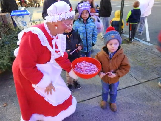 Carol West dressed as Mrs. Santa Claus holds out a