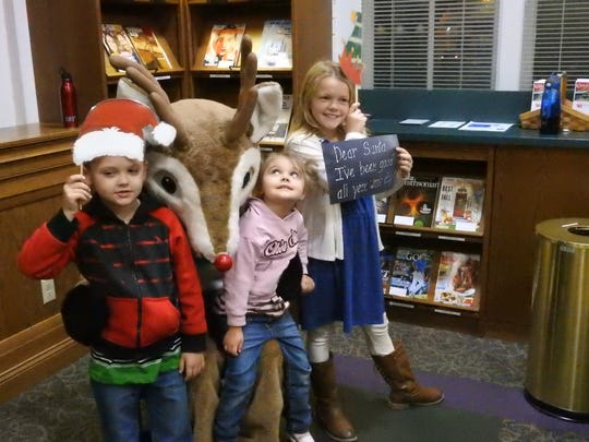 Braydon, Karmen and Haylie Gates have their photo taken with Rudolph the Red-Nosed Reindeer during an open house at the Coshocton Public Library during the Miracle on Main Street parade events in this 2017.