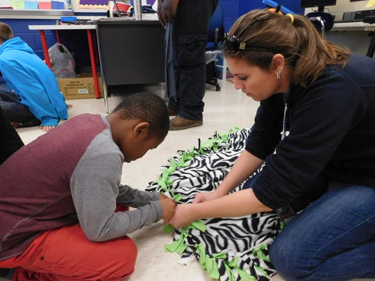 Sara Fisler, K-2 life-skills teacher at Fayetteville Elementary, helps first-grader Dontavious Tubbs with a blanket that will be donated to the Ronald McDonald House at Hershey Medical Center, on Friday, Nov. 17, 2017.