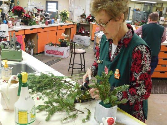 Densie Baranowski cuts greens for a flower arrangement