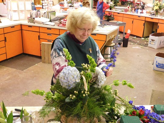 Steph Rice makes a basket arrangement on Friday, Dec. 15, 2017, at Plasterer's Florist. She has been with Plasterer's for 44 years.