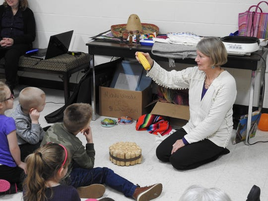 Patti Malenke explains a traditional way from Mexico corn was taken off the cob to students Thursday at the Johnson-Humrickhouse Museum.