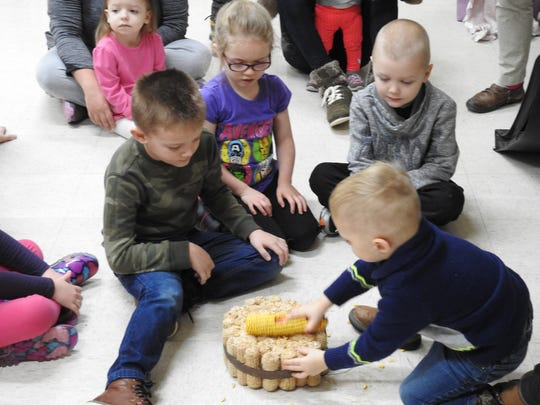 Children try out a traditional way of taking corn off the cob from Mexico during a program on different cultures around the world Thursday at the Johnson-Humrickhouse Museum.