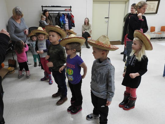 Students try on hats and prepare to do a dance Thursday