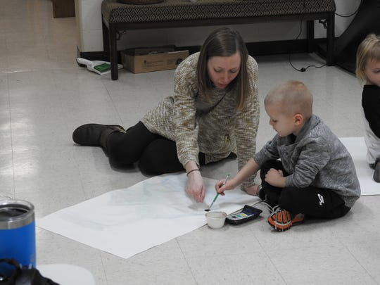Jamie Henderson helps her son, Jack, 5, work on a watercolor painting based on a Chinese vase at the Johnson-Humrickhouse Museum. Preschool students are learning about different cultures each Thursday in January at the museum.