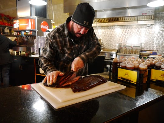 Big Mouth BBQ co-owner Sean Knox slices into a beef brisket. Big Mouth won the 2018 Greatest of Great Falls barbecue category.