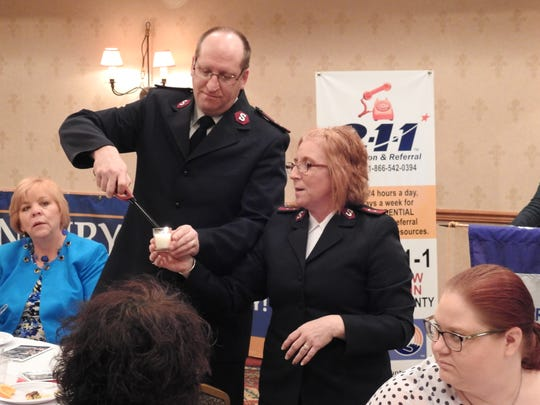 Captains Tom and Vicki Clark of the Coshocton County Salvation Army light a candle during the United Way of Coshocton County's annual breakfast and meeting on Thursday at Coshocton Village Inn and Suites.