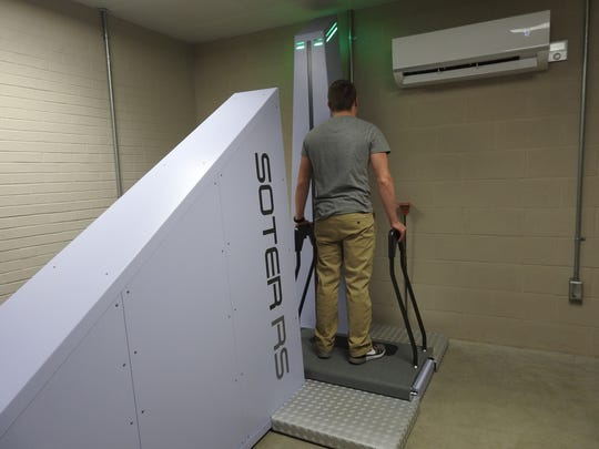 A test subject stands on a new body scanner at the