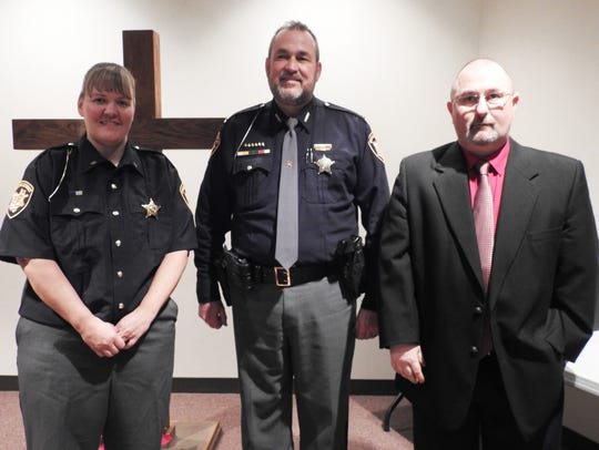 Sheriff Tim Rogers, center, honors Communications Officer