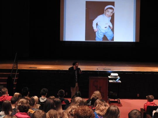 "Sam Drazin shows a picture of himself as a child while talking about his hearing issues to students Thursday of Coshocton Junior High School. Drazin was born with Treacher Collins Syndrome like Auggie in the book and movie ""Wonder."""