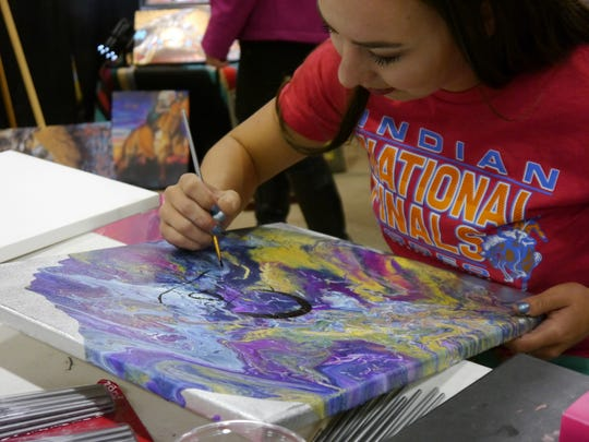 Blackfeet artist Sammy Jo Bird works on a new painting during the Western Living and Design Show Thursday at the Four Seasons Arena.